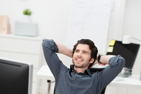 25337053 - successful businessman relaxing in his chair leaning back with his hands behind his head looking into the air smiling